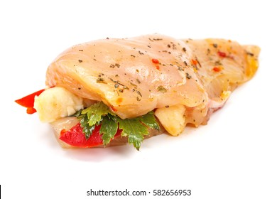 Marinated and stuffed chicken breast fillet with fresh herbs on white background