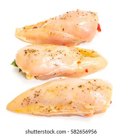 Marinated and stuffed chicken breast fillets on white background