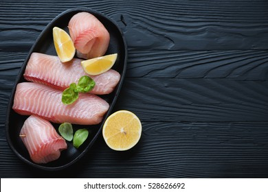Marinated tilapia fillet over black wooden surface with copyspace, top view
