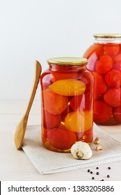 Marinated tomatoes in a jar on a light wooden table