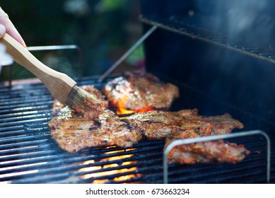 Marinating meat during grilling. Pork on the grill. Barbecue in the garden. Hand with a brush in motion.