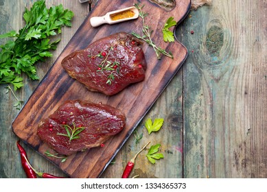 Marinating meat with spices and greenary on wooden table, copy space flat lay