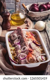 Marinating pork loin with onion on rustic table