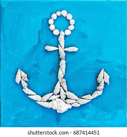 Marine anchor made of seashells on the blue background. Summer vacation theme.