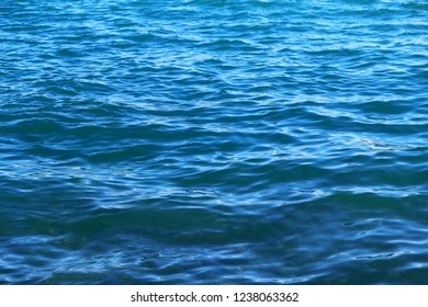 Marine background photo bright blue transparent water with reflections