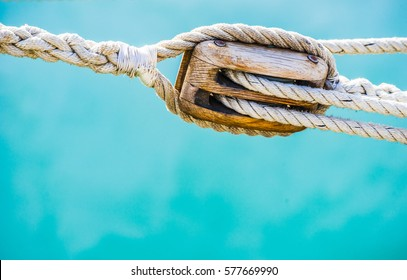 Marine background, sailing boat wooden pulley with nautical rope.