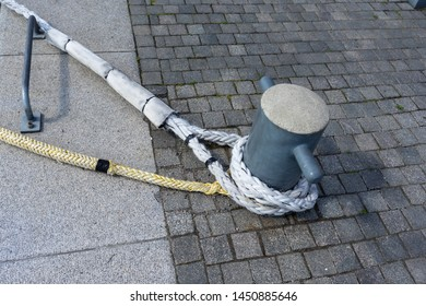 """Marine Bollard column with """"eye-splice"""" on the end of a rope. Close-up of a mooring rope fixed on bollard. Method of creating a permanent loop (an eye) in the end of a rope by means of rope splicing."""