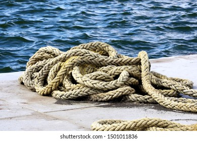 Marine bollard on a dock with yellow rope wrapped around it