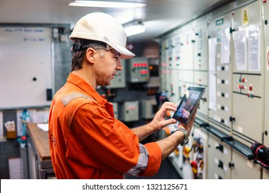 Marine chief engineer watching digital tablet in engine control room. Internet and home connection at sea.