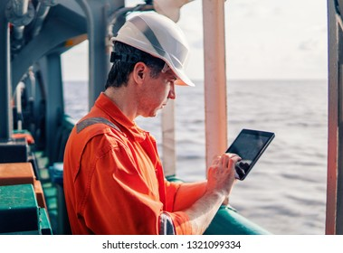 Marine chief officer or captain on deck of vessel or ship watching digital tablet. Internet and home connection at sea.