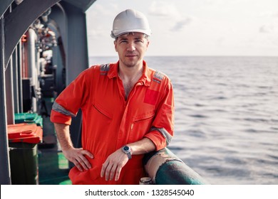 Marine chief officer or chief mate on deck of ship or vessel. He is looking at the camera. He looks happy.