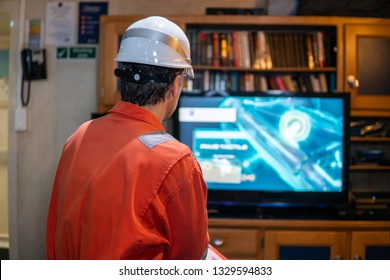 Marine chief officer wearing coverall and helmet on a ship or vessel having fun watching TV. Recreation during at sea