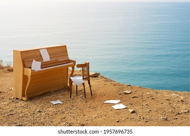 Marine coastal landscape. An old vintage piano on the edge of a cliff by the sea. Sheets of notes flying in the wind. Shore inspiration with copy space.