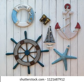marine concept, steering wheel, life ring and anchor on a white wooden wall