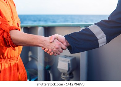 marine contractor businessman handshaking with worker on the ship. Handshake of two boilersuits with different color. Business shipping background