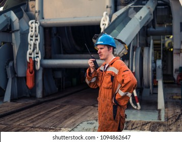 Marine Deck Officer or Chief mate on deck of marine vessel or ship , wearing PPE personal protective equipment - helmet, coverall.He is giving orders to deck crew by radio.