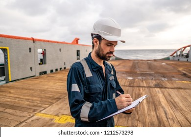 Marine Deck Officer or Chief mate on deck of vessel or ship . He is inspecting and writing checklist. Ship paperwork