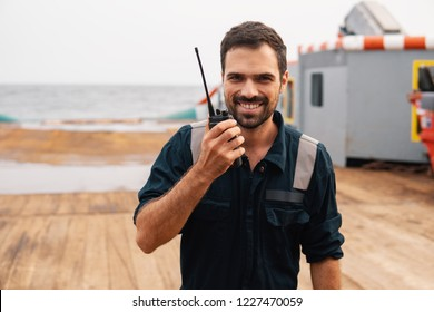 Marine Deck Officer or Chief mate on deck of vessel or ship . He holds VHF walkie-talkie radio in hands. Ship communication