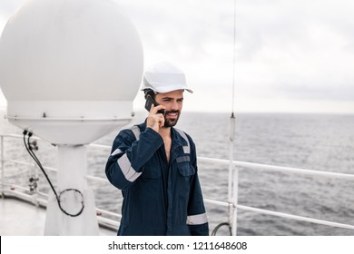 Marine Deck Officer or seaman on deck of vessel or ship . He is speaking on the mobile cell phone