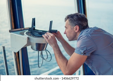 Marine deck officer taking magnetic compass error onboard of vessel at open sea. Job at sea