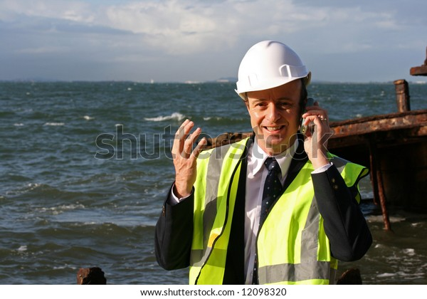 Marine engineer explaining on his mobile telephone that the shipwreck cannot be salvaged, as it had run aground years ago,