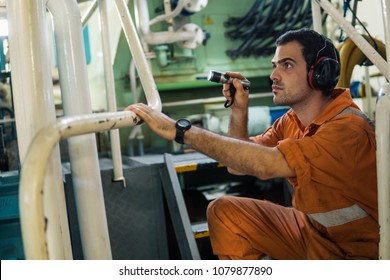 Marine engineer inspecting ship's engine with torchlight in engine control room ECR. Seamen's work.
