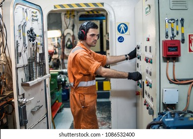 Marine engineer officer controlling vessel engines and propulsion in engine control room ECR. Ship maintenance
