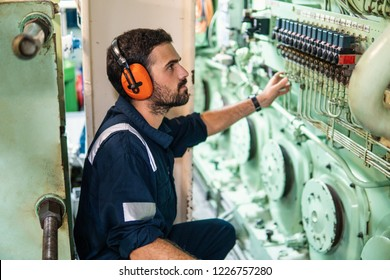 Marine engineer officer in engine control room ECR. Seamen's work. He starts or stops main engine of ship