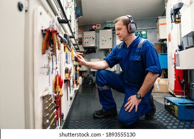 Marine engineer officer in engine control room ECR. He works in workshop and chooses correct tools and equipment