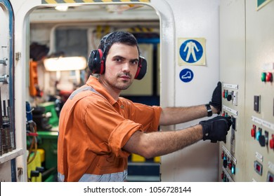 Marine engineer officer starts or stops main engine or generators of ship in engine room. Seamen's work. He wears ear protection.