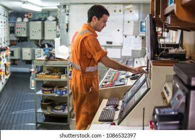 Marine engineer officer starts or stops main engine of ship in engine control room ECR. Seamen's work.