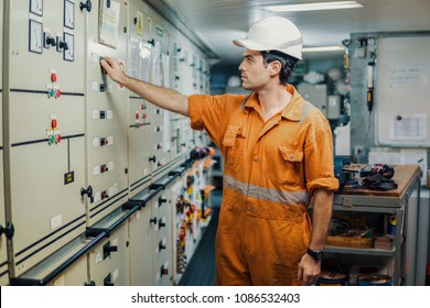 Marine engineer officer starts or stops main engine of ship in engine control room ECR. Seamen's work. He is wearing helmet