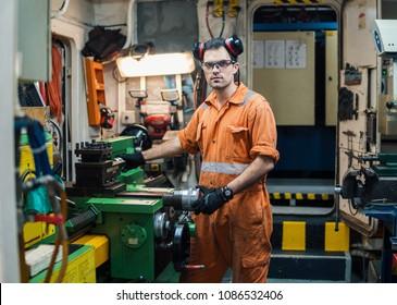 Marine engineer working in ship's workshop in engine control room ECR. Seamen's work.