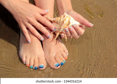 Marine French manicure and pedicure with blue and orange stripes on short nails on the coast in Sunny weather.Nail design.Nail art.