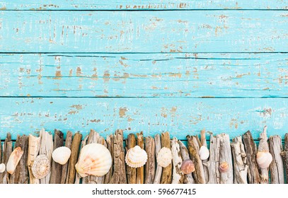 Marine items and sea objects, driftwood and seashells on turquoise blue wooden background.