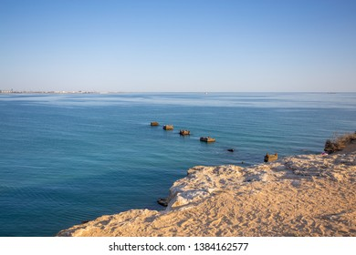 Marine landscape against the blue sky. Caspian sea in Aktau, Kazakhstan. In the foreground is a rocky shore , in turquoise water there are old piles.