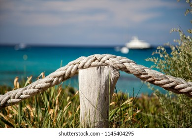 Marine landscape with a rope, a post and bushes in the foreground