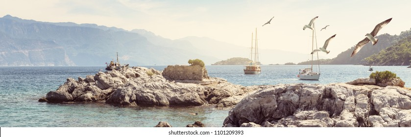 Marine landscape with seagulls - panorama of blue lagoon in Hisaronu bay, Aegean Sea. Cruise to the islands near Fethiye. Romantic trip on sailing yacht to Aquarium beach near Oludeniz resort, Turkey.