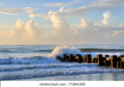 Marine landscape with splashes, scattering from the waves, beating about the remains of the old wooden pier in rising sun lights. Atlantic ocean shoreline, Pawleys Island, South Carolina, USA.