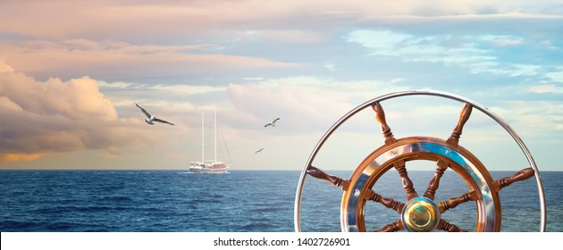 Marine landscape with a steering wheel and sailing yacht on skyline. Calm sea with a cloudy sky at sunrise and flying seagulls for your concept about romantic sea voyage on a ship around the world.