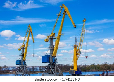 Marine loading cranes of yellow color on a background of blue sky with clouds. Cargo transportation.