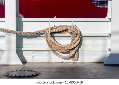 Marine mooring devices. Mooring rope on the ship hanging close-up against the coastline