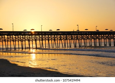 Marine morning landscape with sun rising over the wooden pier with silhouettes of fishermen and umbrellas on it. Garden City beach and pier, South Carolina, USA, Myrtle Beach area.Vacation background.