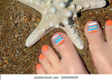 Marine nail design.Pedicure with orange and blue nail Polish on a woman's leg close-up starfish on a background of sea sand.