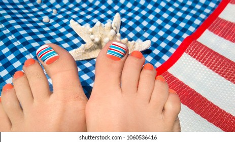 Marine nail design.Pedicure with orange and blue nail Polish on the female foot close - up on a checkered sunbed at the sea during the rest.