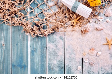 Marine or nautical themed background with a fishing net, starfish and message tied and rolled on scattered beach sand, starfish and shells, copy space below
