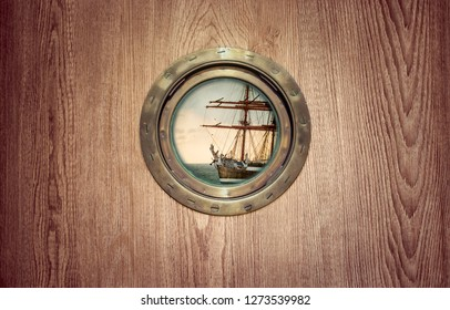 Marine porthole on a wooden ship - round window on ancient sailing vessel. Brass porthole frame on an old sailboat for your nautical poster, concept of seafaring or sea voyage in retro style.