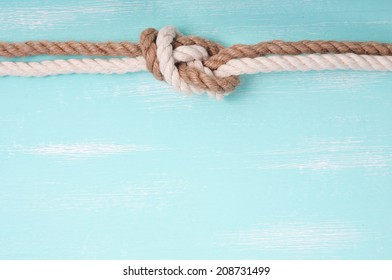 Marine rope with a knot on a wooden background turquoise