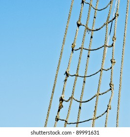 Marine rope ladder at pirate ship. Sea hemp ropes on the old nautical vessel. Ladder upstairs on the mast.