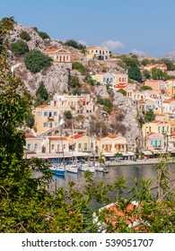 marine sail yachts docked in the port of a small mediterranean town, located on the mountain slopes, view from top of the rock through the trees, Ano Symi city, Simi - one of Dodecanese island, Greece